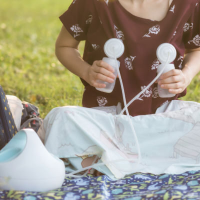 Woman wearing brown top pumping with a Spectra breast pump