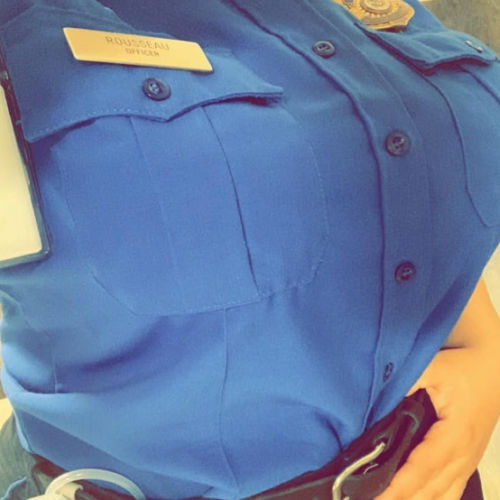 Woman in a blue button down shirt wearing a freemie liberty and pumping while working