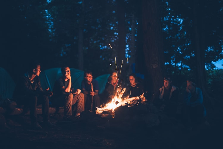 People around a lit campfire in the evening