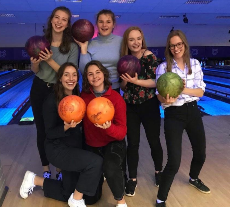 Some happy people posing with bowling balls in front of a bowling alley
