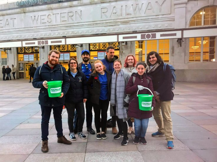 A group of people standing together with fundraising buckets for Macmillan