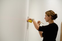 Vita Litvak hangs artists' work for The Wall in Our Heads.