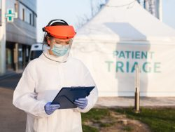 """A female doctor stands with protective equipment and a clipboard in front of a tent that says """"Patient Triage""""."""