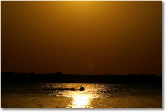 jet ski on Lake Canton in glare of setting sun, Oklahoma
