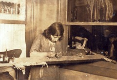 Tenement homework; a girl of 13 working at embroidery in a far corner of a dimly lighted room.