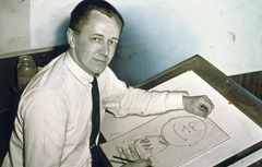 Charles Schulz, half-length portrait, facing front, seated at drawing table with drawing of Charlie Brown (1956).