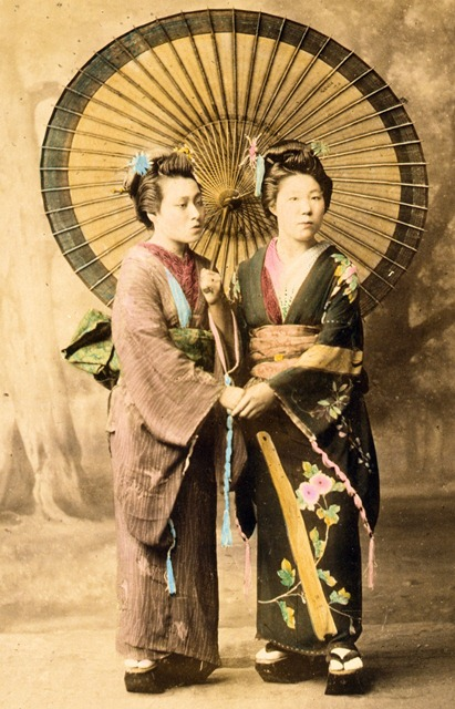 Two Japanese women, full-length studio portrait with backdrop, facing slightly right, standing with large parasol and holding hands