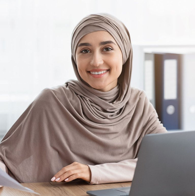 happy-muslim-businesswoman-in-hijab-with-papers-at-P8ZCCJX.jpg
