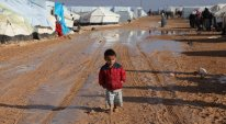 A barefoot child walked through puddles at the Zaatari refugee camp, where about 55,000 Syrians live in hardship. A storm washed away tents last week. Rina Castelnuovo for The New York Times