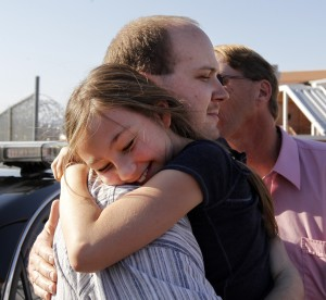Sabrina Hash, 9, hugs her uncle, Michael Wayne Hash after his release from the Albemarle RegionaJail Wednesday, March 14, 2012. His conviction for a 1996 killing was overturned earlier by a judge citing police and prosecutorial misconduct. At right is his father, Douglas Hash.