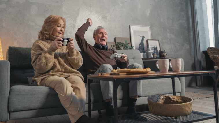 elderly couple sitting on couch playing video games