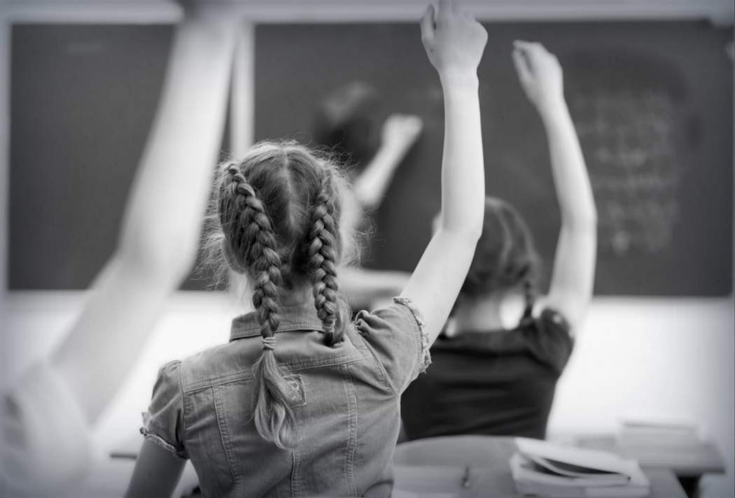 Children with raised hands in a classroom