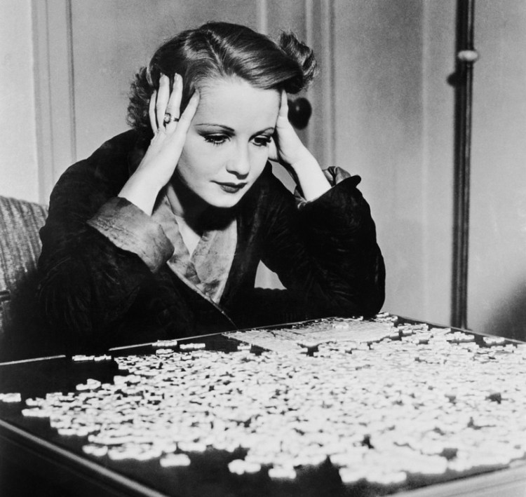 Woman puzzling over a jigsaw puzzle