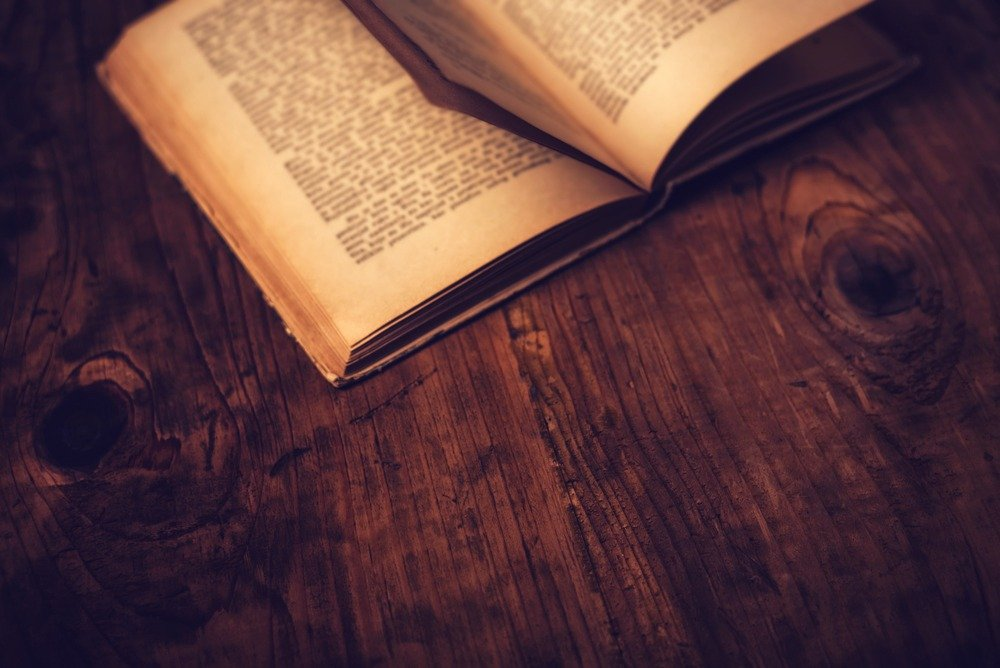 Old book open on wooden table