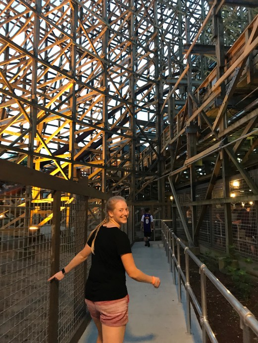 girl turning and smiling with wooden roller coaster beams in the background