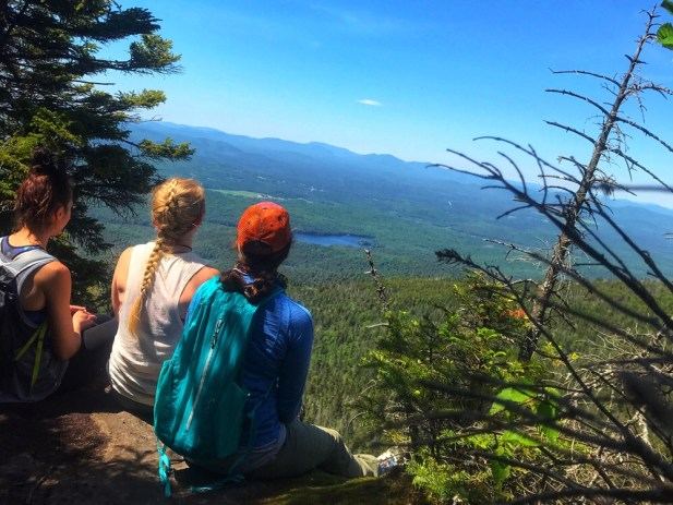 Three girls sit on a ledge looking over Saranac Lake