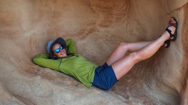 A GIRL LAYING IN A NICE SHADY ALCOLVE ALONG THE SIDE OF THE BUTTE