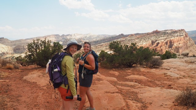 TWO GIRLS IN VERY DIFFERENT SUMMER HIKING ATTIRE ON THE SLICKROCK OF UTAH