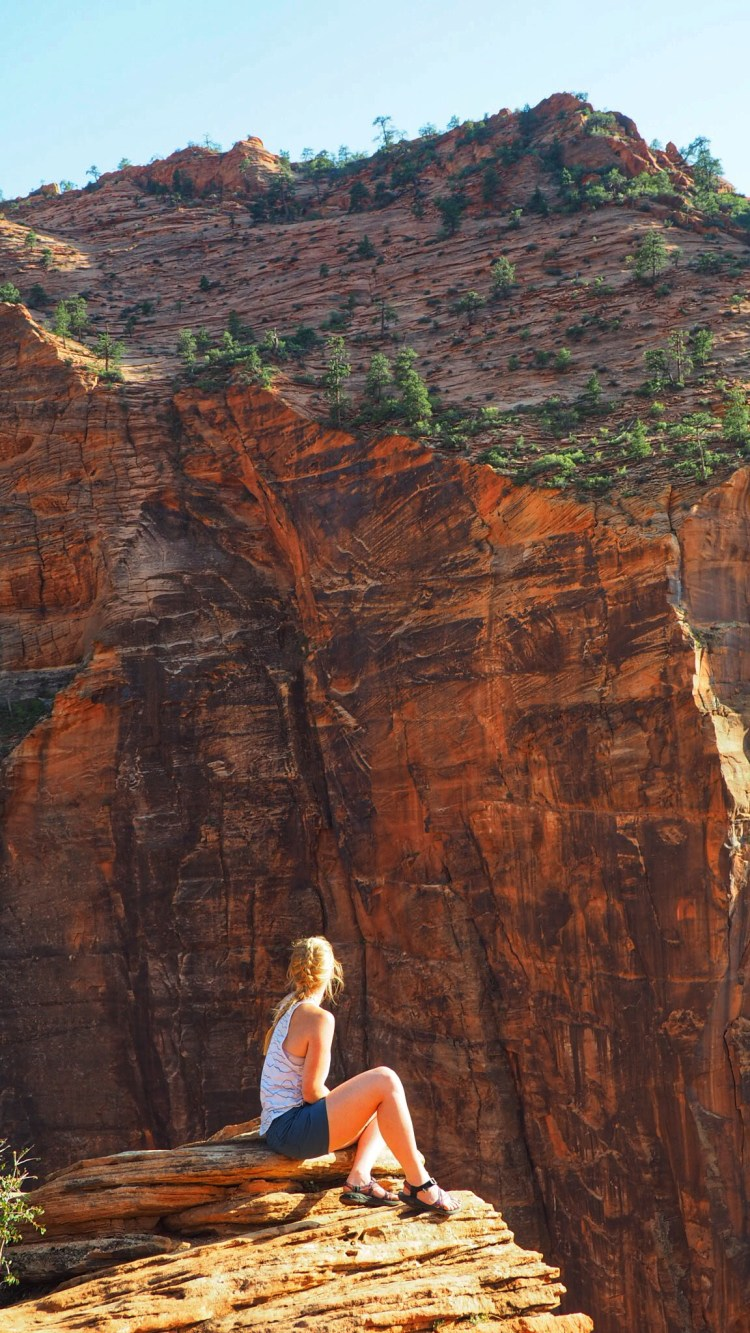 Girl sits on edge on Canyon Overlook Trail in Zion