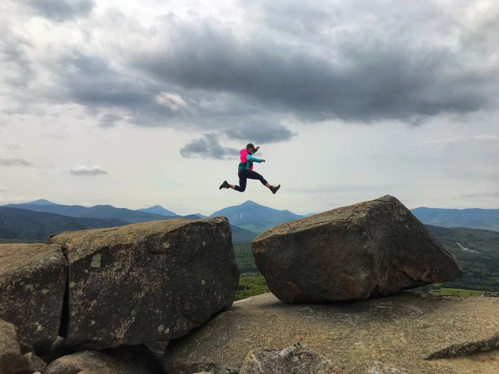 girl jumps from one large boulder to another on a  mountain summit