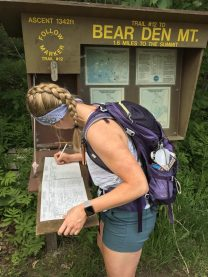 Girl with braid signs into a trail reigster