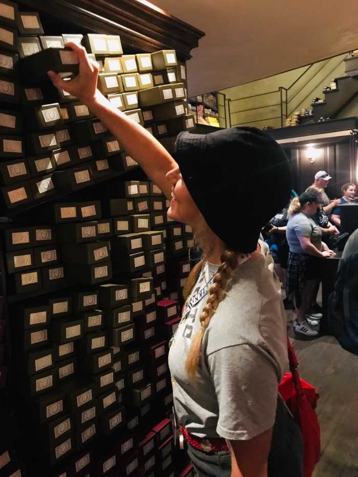 Choosing an interactive wand from the shelves at Ollivanders Wand Shop