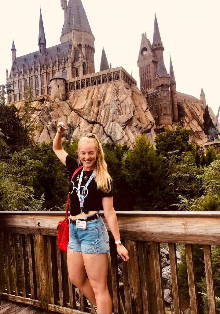 girl with wand in front of hogwarts castle in wizarding world of harry potter  florida