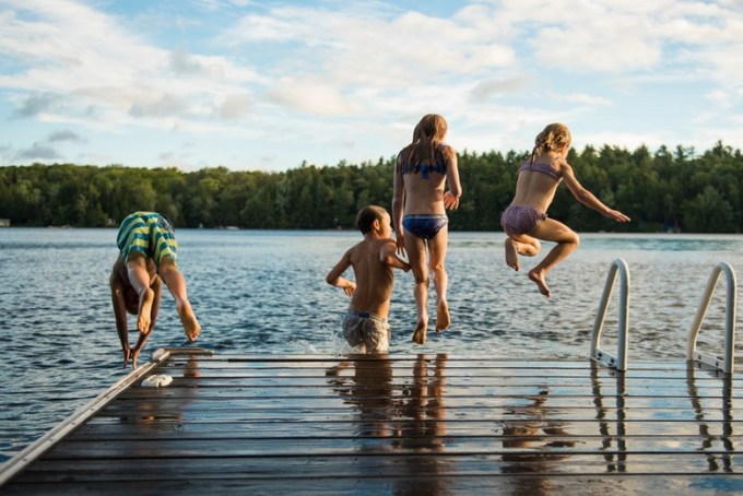 Kids jumping off dock in Rangeley, Maine
