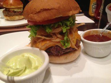 Chipotle - Receita exclusiva com Tabasco® Chipotle. Burger Angus (200g), envolto em bacon, sobre fatias de cebola na chapa com molho especial, cebola à dorê, alface picado e tomate. Servido no pão de hambúrguer tradicional. Foto: ExperiMenteSP