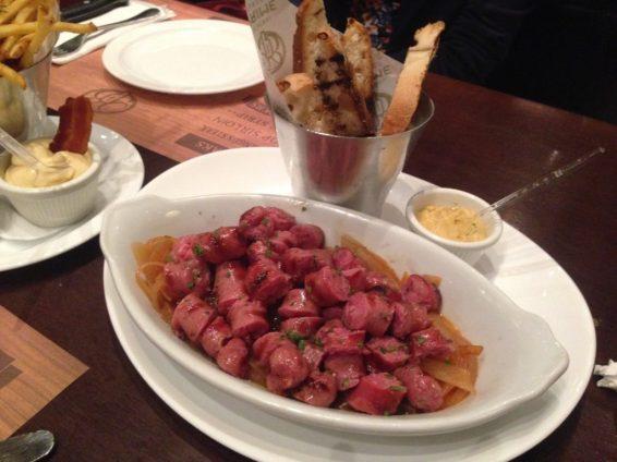 Linguiça de Costela Angus - Linguiça de costela de boi Angus fatiada com cebola caramelizada e mostarda Dijon. Foto: ExperiMenteSP
