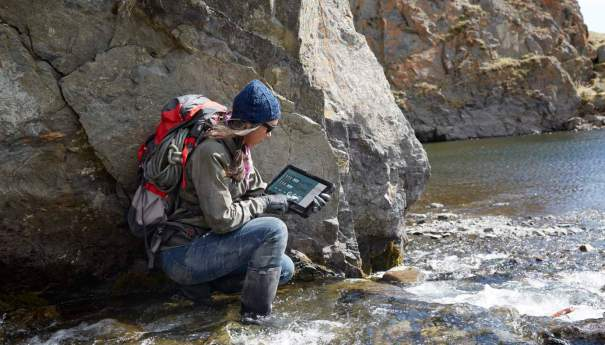 Woman Kneeling in Creek with Latitude 12 Rugged Tablet