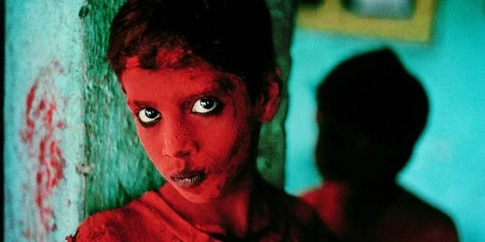 Steve McCurry portrait d'un enfant peint avec de la peinture faciale rouge contre un mur vert - travail de photographes célèbres