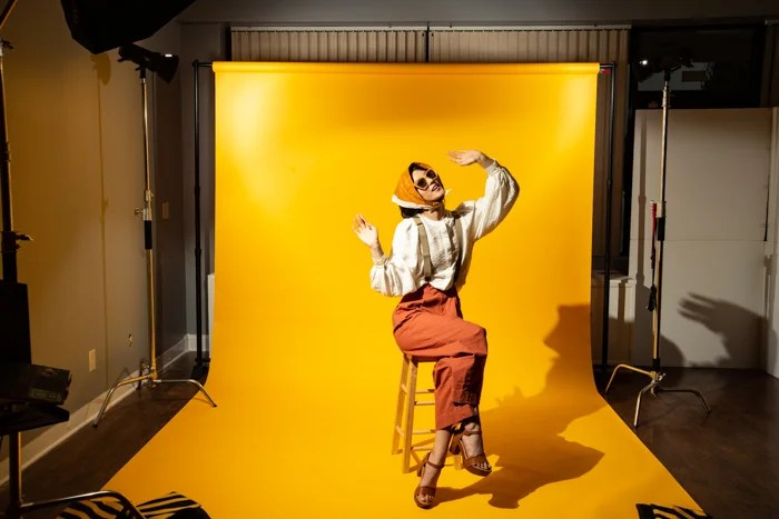 A model posing against a large yellow background
