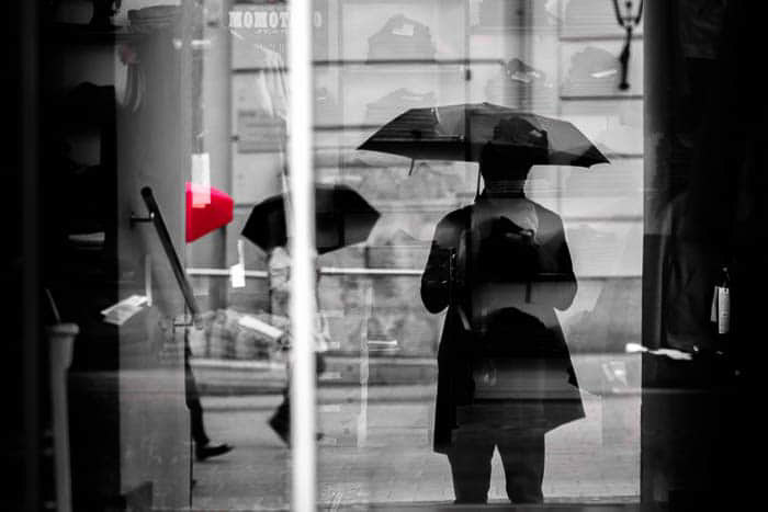 A black and White street photo of people walking in the rain, one umbrella is spot colored red