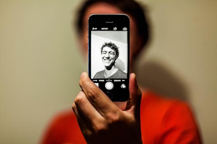 Photo of a guy taking a selfie using an iphone camera app