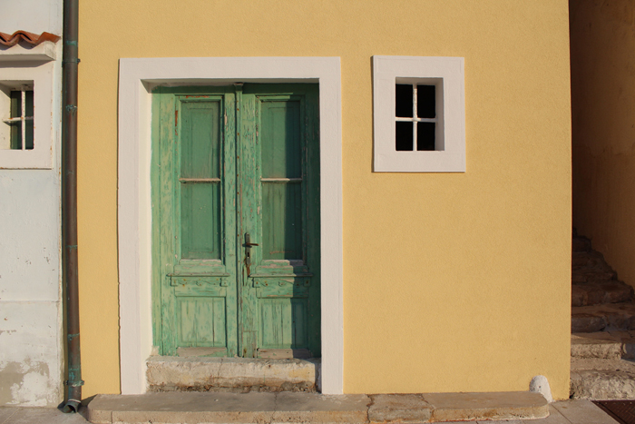 an image of a green door within a yellow building with small window to its right