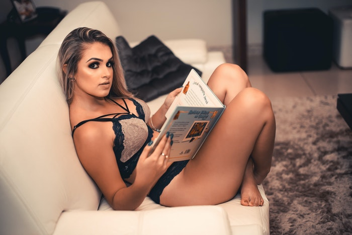 A girl in sexy lingerie posing reading on a couch