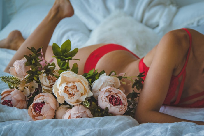 A close up of a girl in red lingerie posing on a bed for a bridal boudoir photoshoot