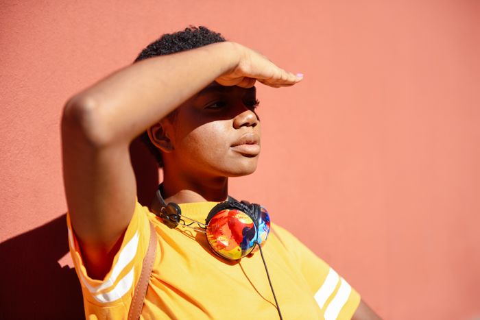 Young black woman covering with her hand the sun that falls on her eyes. Girl with very short hair.