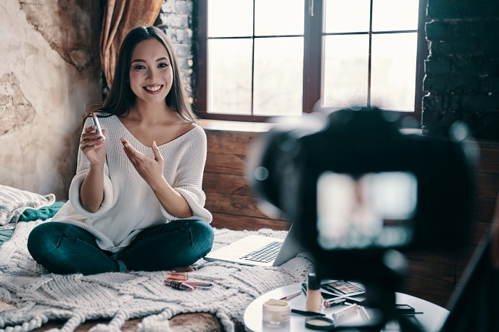 Young woman holding lipstick and smiling at a camera sitting on bed