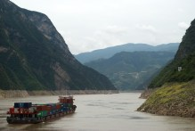 Shipping containers make their way down the river on a barge.
