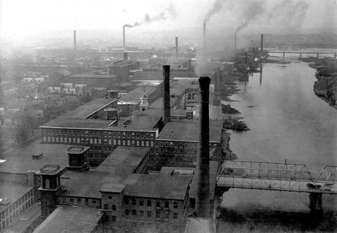 """View of buildings on the Merrimack River. Boott Mill in foreground (Clock tower visible in middle of mill complex)"". (Source: university of Massachusetts. Taken from the top of the new chimney of Massachusetts Mill. October 31, 1910)."
