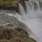 Kayaker heading over the edge of a waterfall