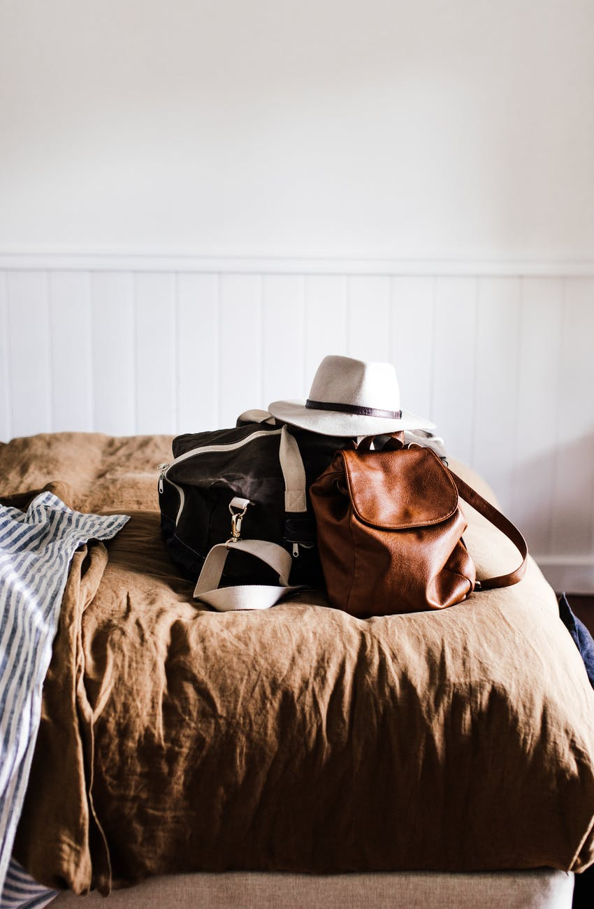 baggage with hat on soft bed in house
