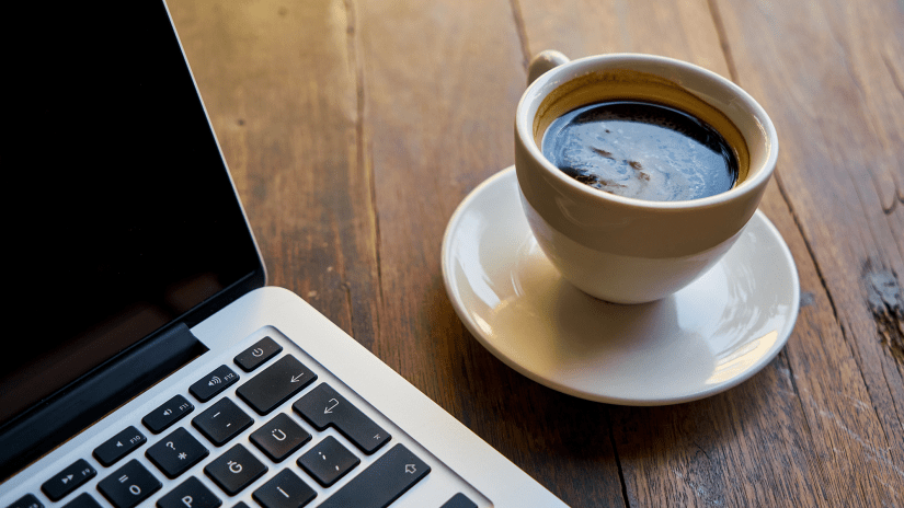 Image of coffee next to laptop