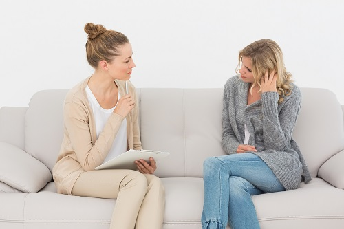 Upset woman talking to her therapist on the couch at therapy ses