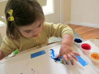 toddler painting with hands