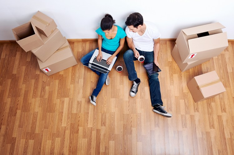 Couple sitting on floor with laptop surrounded by boxes