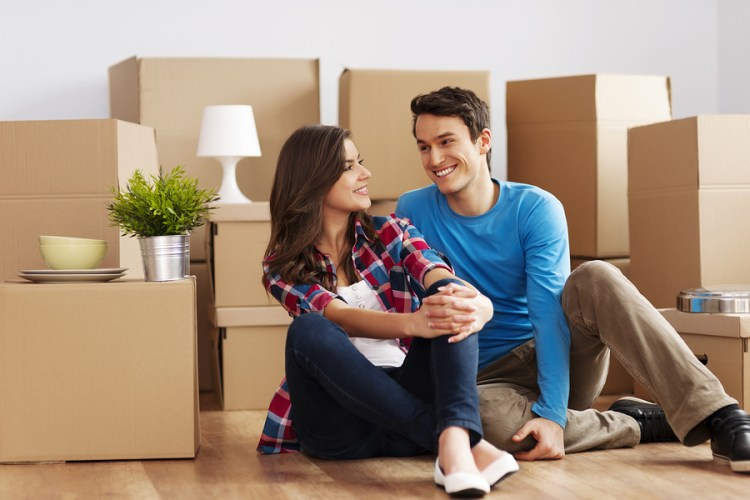 Couple moving to new house surrounded by boxes