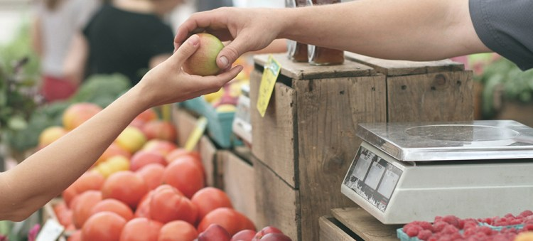 Person handing fruit at farmer's market